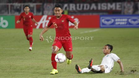 Febri Haryadi berhasil melewati penjagaan pemain belakang Timor Leste.