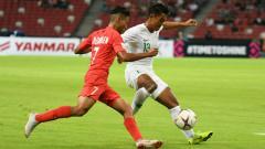 Indosport - Febri Hariyadi saat berduel merebut bola dengan pemain Singapura.