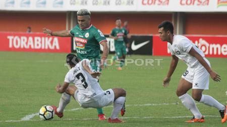 Cristian Gonzales mencoba melewati adangan pemain lawan. - INDOSPORT