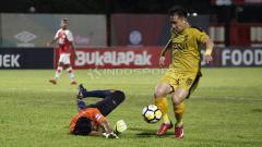 Indosport - Pemain Bhayangkara FC. Lee Yujun (kanan) mencoba melewati kiper Persipura, Dede Sulaiman.