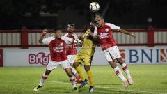 Indosport - Ricardo Salampessy menghalau bola yang mengarah ke Vendry Mofu.