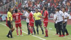Indosport - Wasit memberikan kartu kuning kepada pemain Persija Jakarta