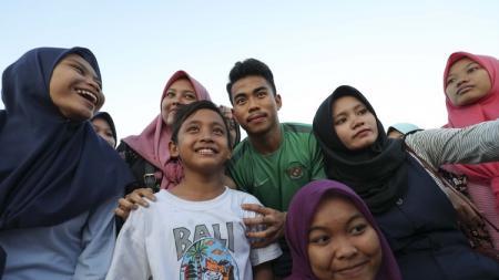 Pemain Timnas Indonesia U-19, Nurhidayat Haji Haris berswafoto bersama penggemar usai sesi latihan di Stadion Jenggolo, Sidoarjo, Jawa Timur, Minggu (8/7/2018). - INDOSPORT