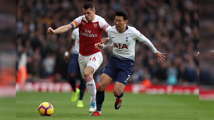 Son berusaha merebut bola dari Granit Xhaka di pertandingan Arsenal vs Tottenham Hotspur Copyright: Getty Images