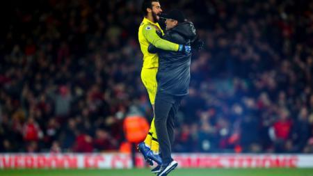 Jurgen Klopp merayakan kemenangan Liverpool bersama Alisson Becker di laga Liverpool vs Everton. - INDOSPORT