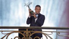 Indosport - Kylian Mbappe saat menerima piala Trophee Kopa di acara Ballon d'Or.