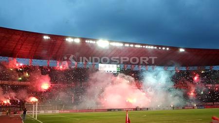 Pendukung Persebaya, Bonek menyalakan flare usai laga pekan ke-34 Liga 1 2018. - INDOSPORT