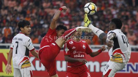 Pemain Persija Jakarta dan Mitra Kukar berusaha merebut bola yang melambung di udara.