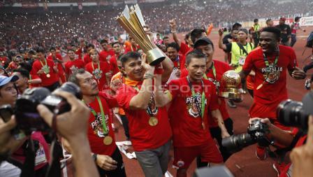 Pemain Persija Jakarta, Ismed Sofyan mengangkat tropi Liga 1, merayakan kemenangannya.