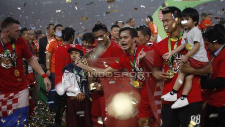 Pemain Persija Jakarta mengangkat tropi Liga 1, merayakan kemenangannya.