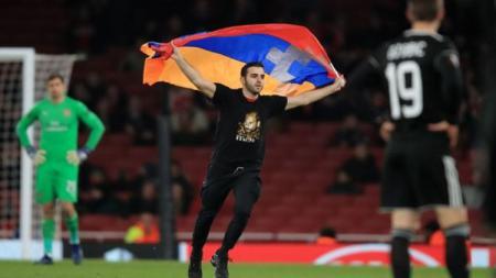 Seorang pria menerobos masuk ke lapangan saat laga Arsenal vs Qarabag - INDOSPORT