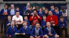 Indosport - Mohamed Salah, Andy Robertson dan Xherdan Shaqiri memberi kejutan natal ke anak sekolah Merseyside