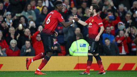 Paul Pogba berselebrasi bersama Juan Mata usai mencetak gol ke gawang Huddersfield. - INDOSPORT