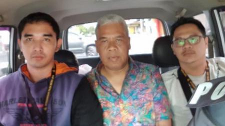 Anggota Komisi Disiplin PSSI Dwi Irianto alias Mbah Putih (tengah) diciduk Satgas Anti Mafia Bola dari Hotel New Saphire, Yogyakarta, Jumat (28/12/2018). - INDOSPORT