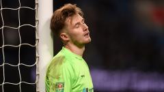 Indosport - Bradley Collins kiper Burton tertunduk lesu setelah kalah banyak oleh Manchester City
