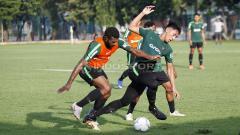 Indosport - Hanif Sjahbani (tengah) berebut bola dengan Marinus Wanewar.