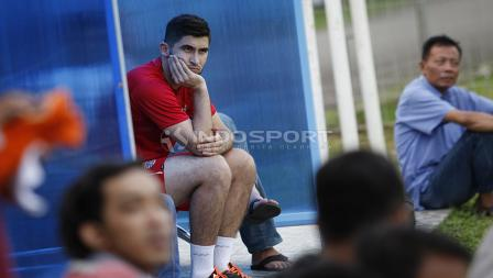 Pemain anyar Persija, Jakhongir Abdumuminov menyaksikan rekan-rekannya berlatih dari pinggir lapangan.