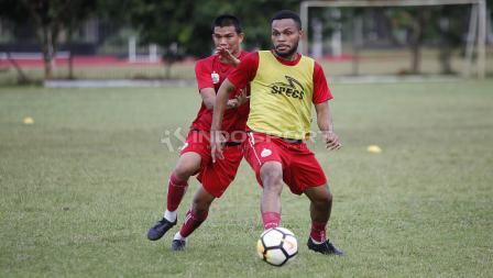 Sandi Sute (kiri) berebut bola dengan rekannya dalam latihan.