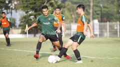 Indosport - Wahyudi Hamisi (kanan) melakukan passing kepada rekannya.