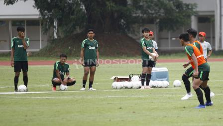 Para pemain yang tidak memakai rompi menyaksikan rekannya berlatih sambil menunggu giliran.