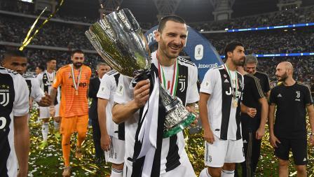 Leonardo Bonucci tengah membawa trofi Supercoppa Italiana sambil tersenyum dengan menghadap salah kamera.