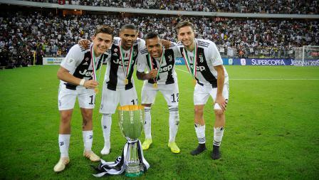 Paulo Dybala, Douglas Costa, Alex Sandro dan Rodrigo Bentancur melakukan foto bersama trofi yang baru mereka peroleh.