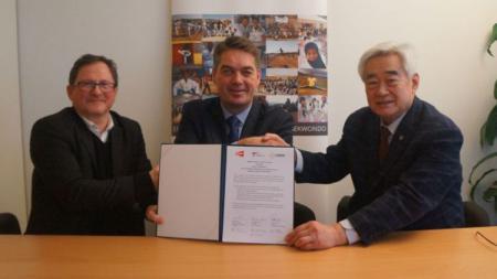 Poul-Erik Hoyer (tengah) saat menandatangani kesepakatan kerja sama dengan taekwondo. - INDOSPORT