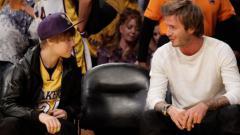 Indosport - Justin Bieber ketika menonton pertandingan basket bersama David Beckham pada 2010 lalu.