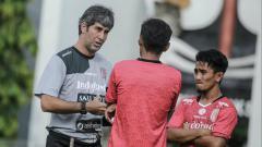 Indosport - Stefano Cugurra Teco memberikan arahan kepada pemain Bali United dalam sesilatihan.