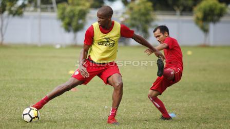 Neguete (kiri) berebut bola dengan Riko Simanjuntak.