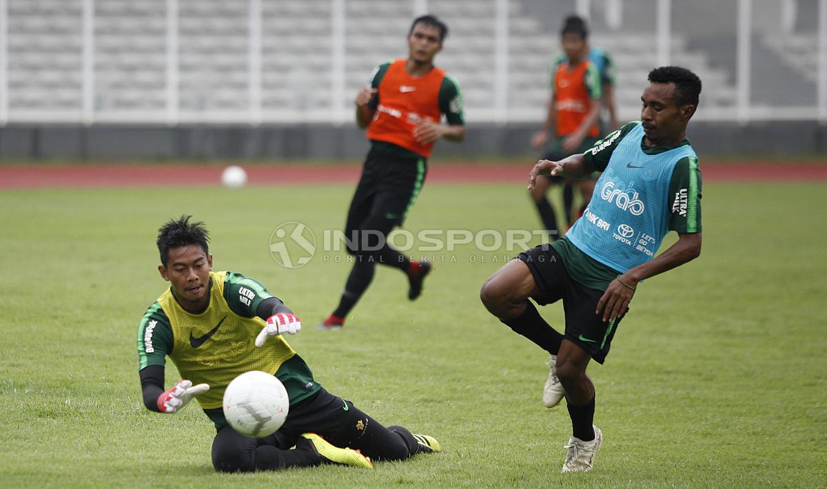 Kiper Satria Tama (kiri) menggagalkan peluang yang didapat Todd Rivaldo Ferre. Copyright: Herry Ibrahim/Indosport.com