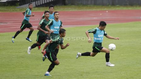 Aksi Wahyudi Hamisi menguasai bola (kanan).
