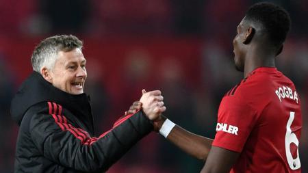 Caretaker Manchester United Ole Gunnar Solskjaer (kiri) berjabat tangan dengan gelandang Paul Pogba (kanan). - INDOSPORT