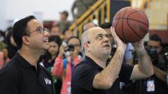 Indosport - Head Coach Jr. NBA, Carlos Barroca (kanan) mencontohkan cara melempar bola basket yang benar kepada Gubernur DKI Jakarta, Anies Baswedan.