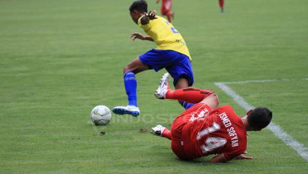 Ismed Sofyan terjatuh setelah dihadang oleh pemain belakang 757 Kepri