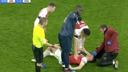 Laurent Koscielny menerima perawatan usai menerima sepakan kaki di wajahnya oleh Romelu Lukaku - INDOSPORT