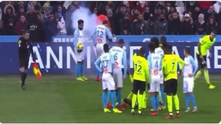 Pemain Olympique Marseille hampir terkena serangan kembang api dari tribune penonton. - INDOSPORT