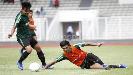 Firza Andika (kanan) terjatuh saat berebut bola dengan Witan Sulaiman.