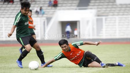 Firza Andika (kanan) terjatuh saat berebut bola dengan Witan Sulaiman. - INDOSPORT