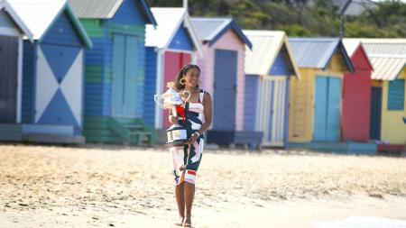 Naomi Osaka ketika berjalan di pantai sembari membawa trofi Australia Terbuka 2019. - INDOSPORT