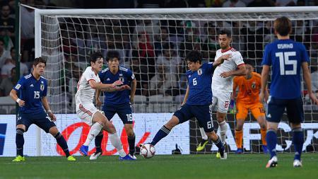 Wataru Endo (Jepang) membuang bola saat pemain Iran berusaha membobol gawang Jepang. - INDOSPORT
