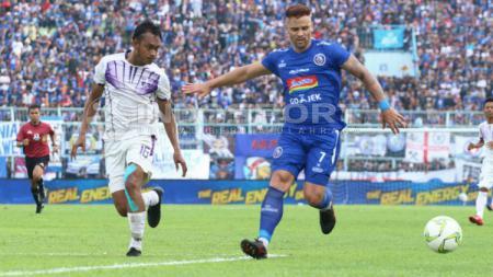 Pemain Arema FC Robert Lima Guimaraes dibayangi bek Persita, Rio Ramandika. - INDOSPORT