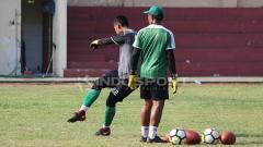 Indosport - Pelatih kiper Persebaya Miftahul Hadi melihat latihan anak didiknya di Lapangan Polda Jatim. Rabu (30/01/19).