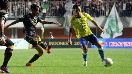 Striker Barito Putera, Samsul Arif, menguasai bola dibayangi gelandang PSS Sleman, Sidik Saimima. - INDOSPORT