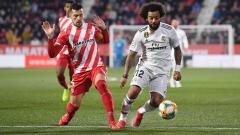 Indosport - Marcelo (kanan) mengindarkan bola dari kejaran pemain Girona.