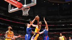 Indosport - Salah satu pemain LA Clippers berusaha gagalkan aksi LeBron James