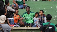 Indosport - Amido Balde menjadi sasaran foto selfie dari Bonek setelah latihan di Lapangan Jenggolo, Sidoarjo selesai. Selasa (5/2/19).