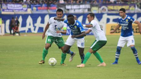 Ezechiel N'Douassel melewati dua pemain Persiwa. - INDOSPORT