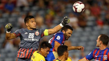Kiper klub Liga Indonesia Persija Jakarta, Andritany terbang meninju bola untuk menghalau serangan pemain Newcastle Jets. - INDOSPORT