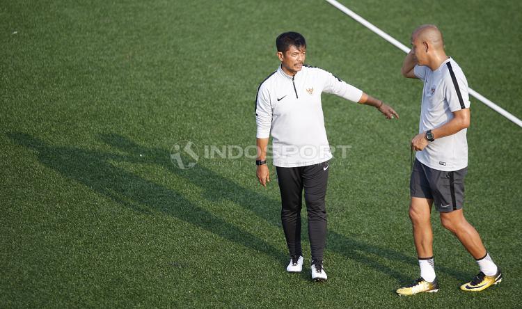 Pelatih Timnas Indonesia U-22 Indra Sjafri tengah berbicara dengan salah satu jajarannya. Copyright: Herry Ibrahim/INDOSPORT